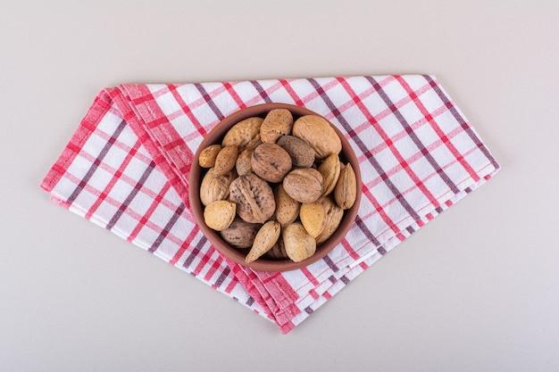 Чаша очищенных от скорлупы органических миндалин и грецких орехов на белом фоне. фото высокого качества