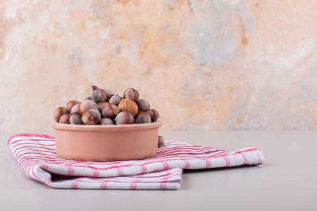 껍질을 벗긴 유기농 헤이즐넛의 그릇은 흰색 배경에 놓여 있습니다. 고품질 사진