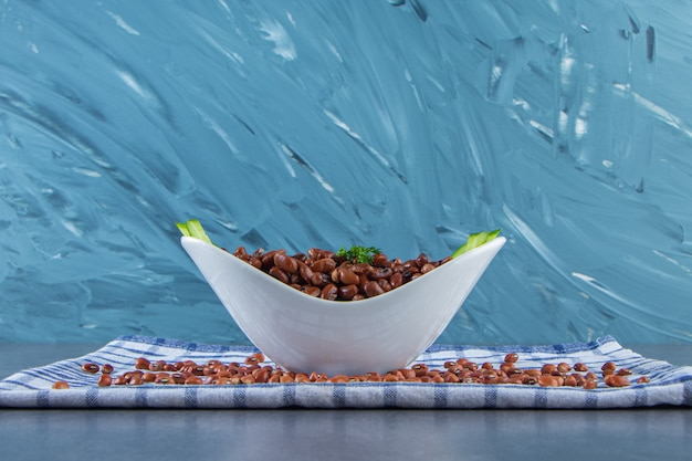 대리석 표면에 수건에 얇게 썬 오이와 콩의 그릇