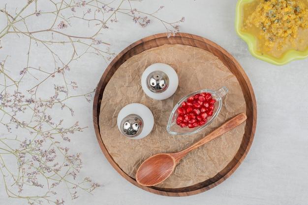 Чаша супа, соли и семян граната на белом.