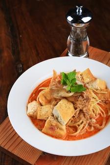 채소로 장식 된 빵 조각, 고기, 스파게티가 들어간 수프 그릇