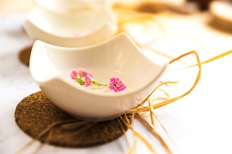 Bowl of spa massage oil on coaster