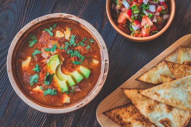 Чаша острого мексиканского супа с жареными лепешками и сальсой