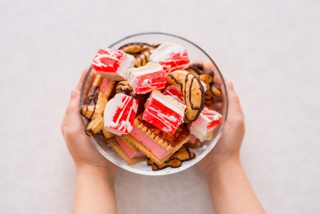 Чаша сладкого десерта в ваших руках. печенье и мармелад на белом фоне