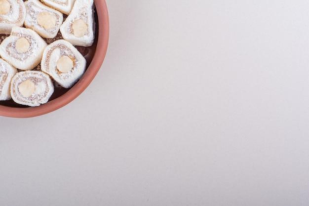 Чаша сладкого десерта лукум с орехами на белом фоне. фото высокого качества