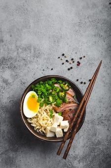 회색 소박한 콘크리트 배경에 국물, 두부, 돼지고기, 계란을 넣은 맛있는 아시아 누들 수프 라면 한 그릇, 텍스트를 위한 공간, 클로즈업, 위쪽 전망. 복사 공간이 있는 저녁 식사로 뜨거운 맛있는 일본 라면 수프