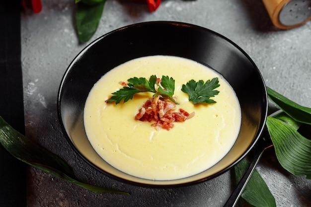 灰色のベーコンとおいしいチーズクリームスープのボウル