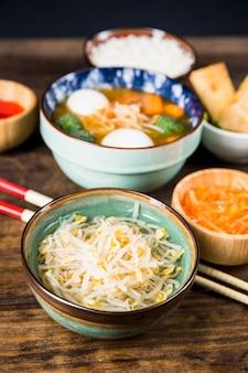 나무 책상에 태국 콩 새싹과 생선 공 수프 그릇