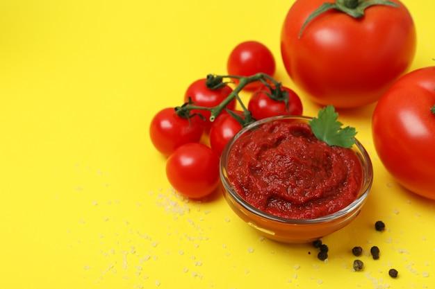 토마토 페이스트와 노란색 배경에 재료의 그릇