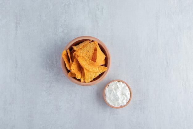 토르티야 칩 한 그릇과 돌 위에 특별한 소스.
