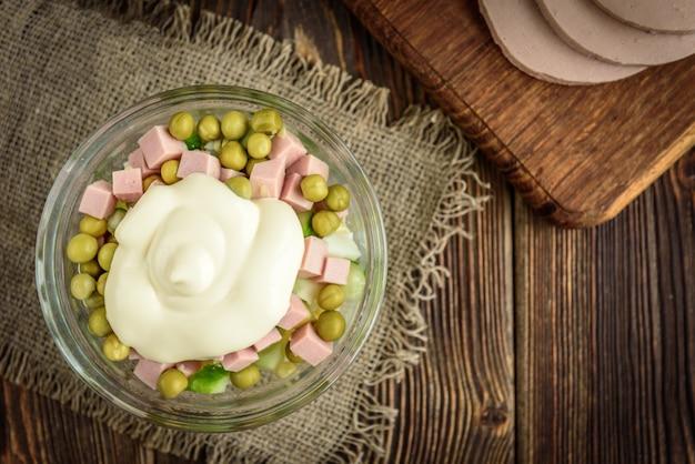 Чаша традиционного русского салата «оливье» и ингредиенты: вареная колбаса, огурец, яйца, горох и майонез на темном деревянном столе.