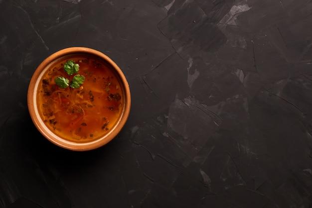 黒いテーブルに伝統的なスープボルシチのボウル。フラット横たわっていた。コピースペース。