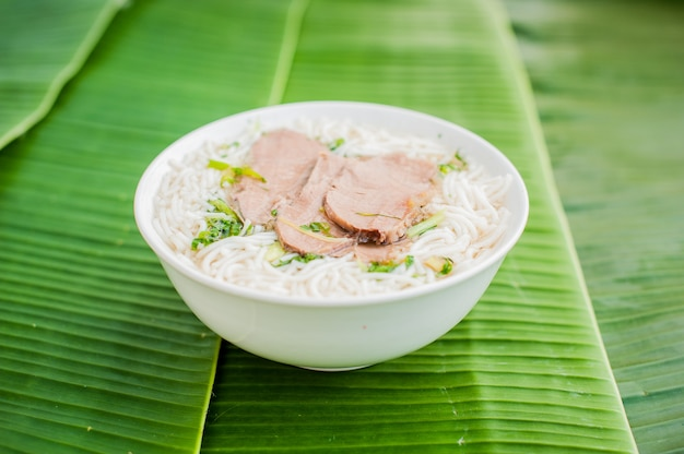 바나나 잎 배경에 전통적인 베트남어 쇠고기 수프 pho bo의 그릇.