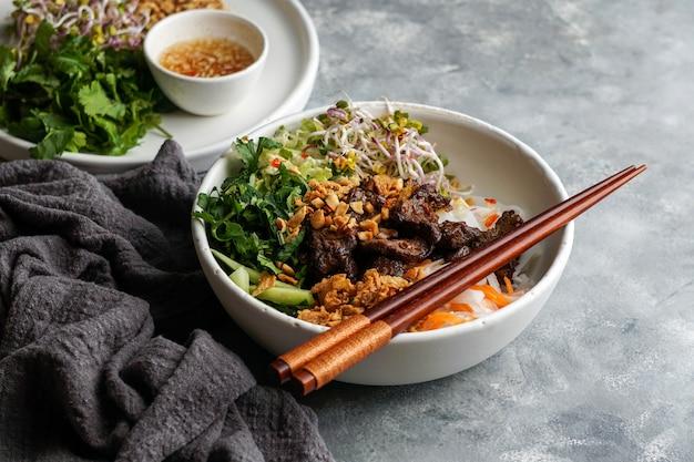 伝統的なベトナムヌードルサラダのボウル-bun bo nam bo、ビーフ、ライスヌードル、フレッシュハーブ、漬物、魚醤