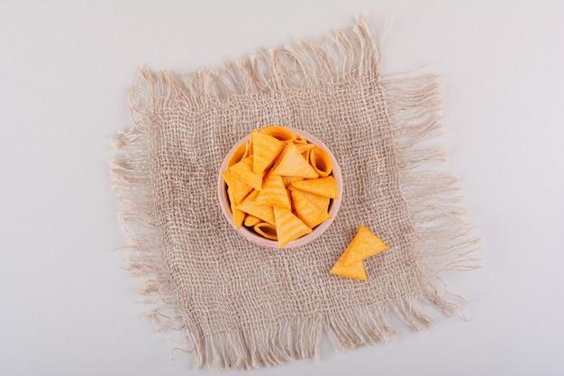 대리석 배경에 놓인 삼각형의 바삭한 칩 한 그릇. 고품질 사진