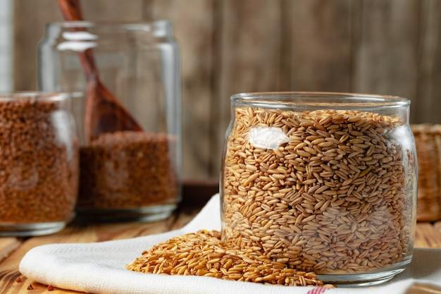 キッチンテーブルの上の未調理の全オート麦粒のボウル