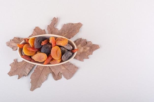 白い背景の上の乾燥した葉を持つ様々な有機フルーツのボウル。高品質の写真