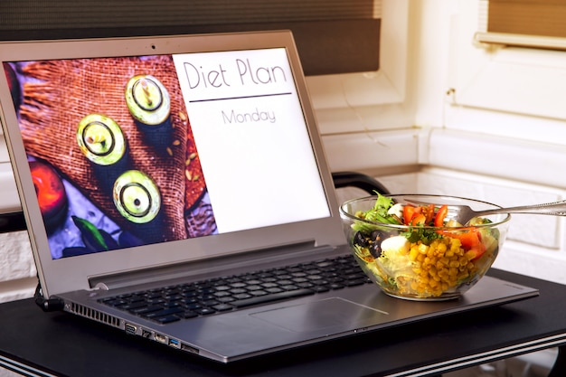 Чаша из овощного салата возле ноутбука на рабочем столе. на экране - планирование диеты для похудения с понедельника