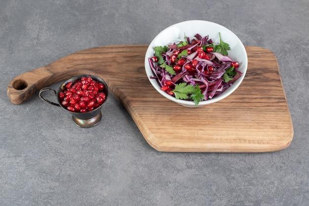 석류 씨와 나무 보드에 야채 샐러드 그릇. 고품질 사진