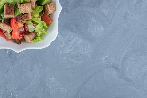 Чаша овощного салата с помидорами, огурцами, салатом и сушеной корочкой на мраморном столе.