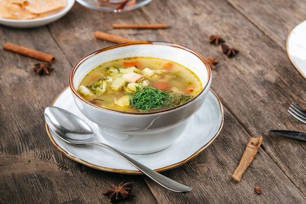 Чаша овощного супа с курицей на деревянном столе
