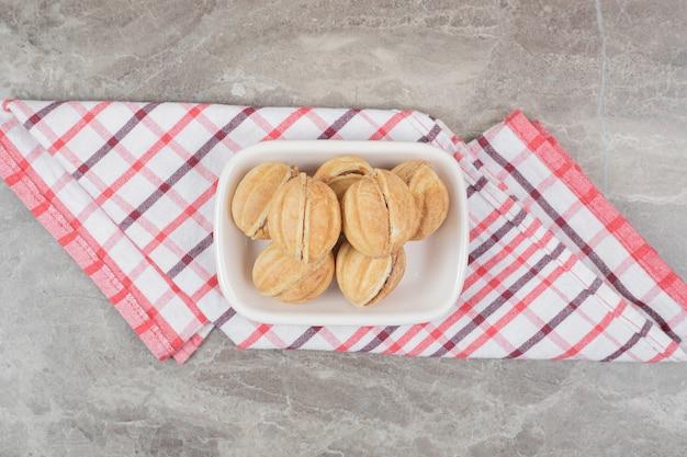 テーブルクロスにくるみの形をしたクッキーのボウル。