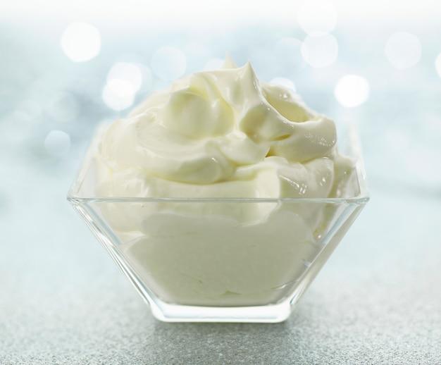 光沢のあるお祭りのボケ味の背景にホイップマスカルポーネチーズクリームのボウル