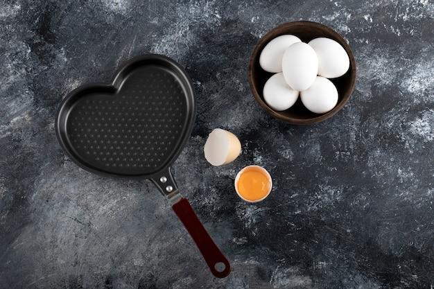 Миска с белыми яйцами и желтком рядом с сковородой в форме сердца.