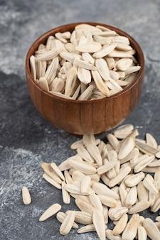 흰 해바라기 씨앗의 그릇 대리석 표면에 흩어져.