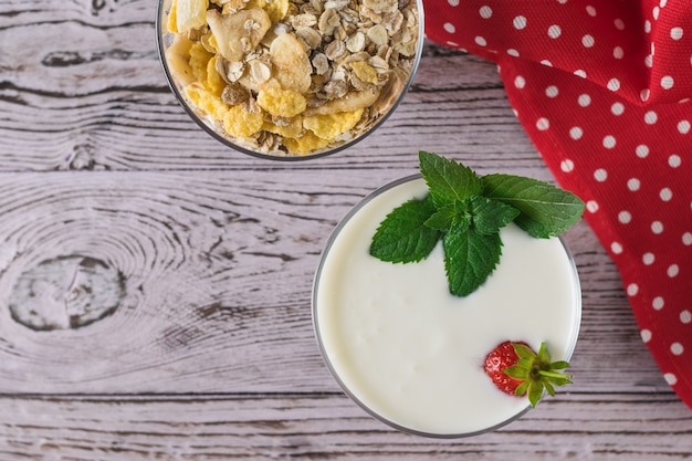 木製のテーブルの上にミントとオートミールのボウルとヨーグルトとイチゴのボウル。美味しくて健康的で栄養価の高い自然食品。上からの眺め。