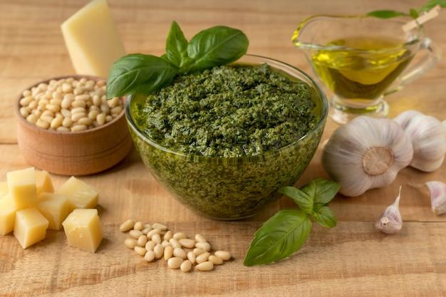 Чаша с вкусным зеленым соусом песто и ингредиентами на деревянном столе