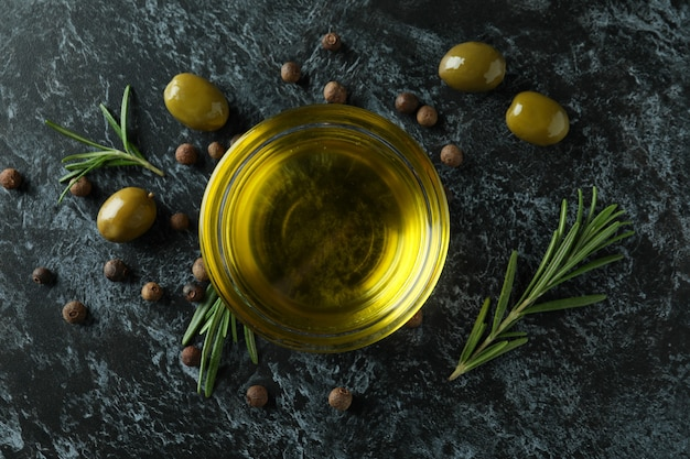 Bowl of olive oil, olives, pepper and rosemary on black smokey