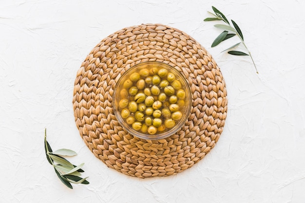 Bowl of olives on coaster with two twigs over the white background