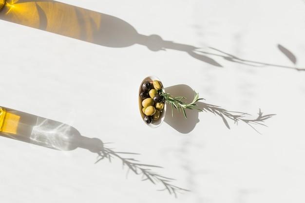 Ciotola di olive con ombra della bottiglia di olio su sfondo bianco