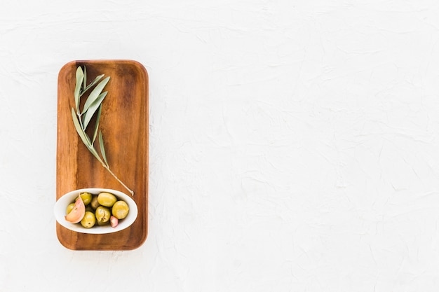 Ciotola di olive con ramoscello sul bordo di legno sopra lo sfondo bianco