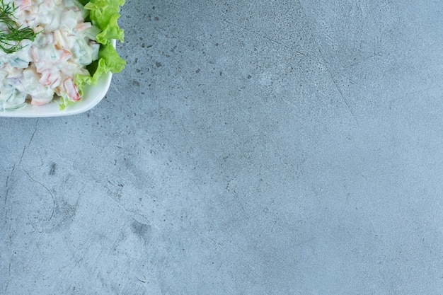 Ciotola di insalata olivier con una foglia di lattuga su marmo.