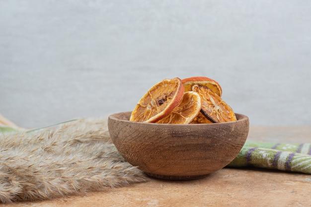 Ciotola di fette d'arancia con tovaglia sulla superficie in marmo.