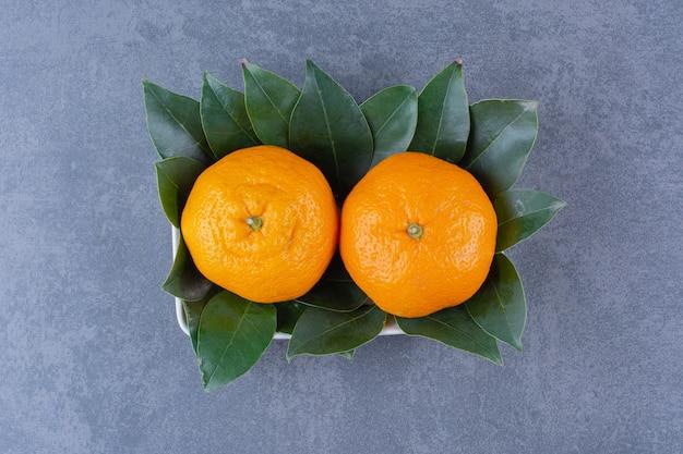 Una ciotola di arance e foglie, sulla superficie scura