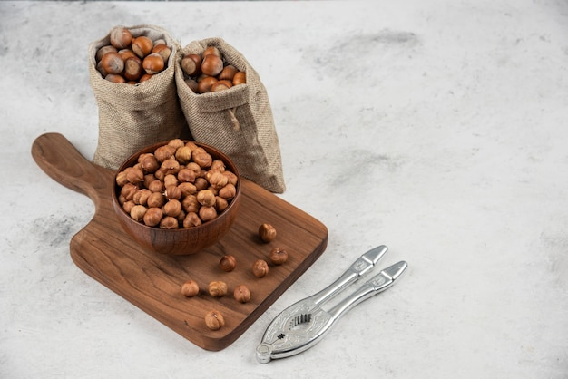 Bowl of organic hazelnut kernels on cutting board with shelled hazelnuts.