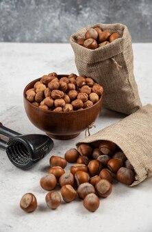 Bowl of organic hazelnut kernels and shelled hazelnuts on marble table.