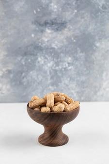 Ciotola di arachidi organiche in guscio isolato sulla superficie bianca