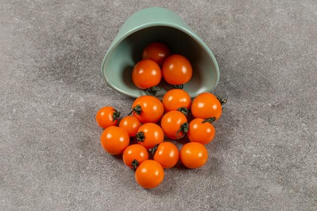 Una ciotola di pomodori rovesciati, sul marmo.