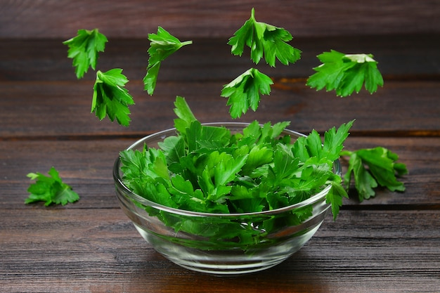 A bowl of parsley with flying leaves on a wooden table. levitation.