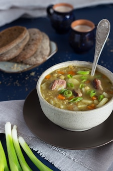 Bowl of pea soup with bread and milk