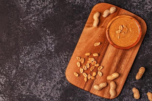 Bowl of peanut butter on wooden breakfast board