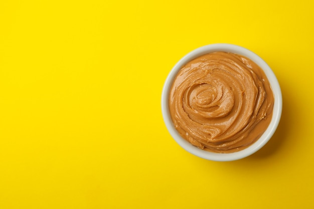 Bowl of peanut butter on yellow background