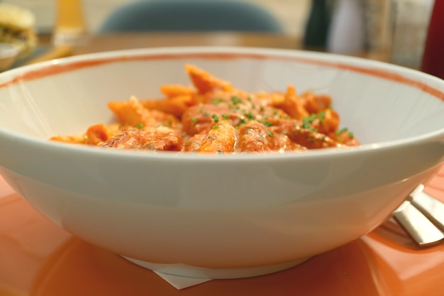 Bowl of penne pasta with shrimp and spicy arrabbiata sauce