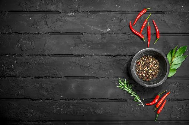 소박한 테이블에 뜨거운 붉은 고추, 베이 리프, 로즈마리와 그릇 고추 완두콩