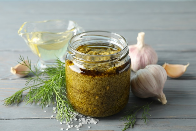 Bowl of pesto sauce, garlic, olive oil, salt on gray background, space for text. closeup