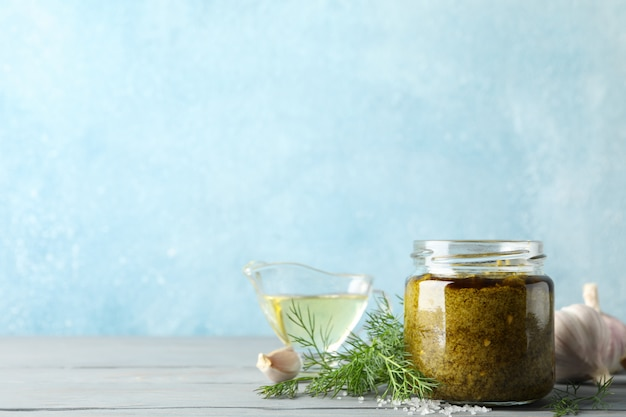 Bowl of pesto sauce, garlic, olive oil, salt on gray background, space for text